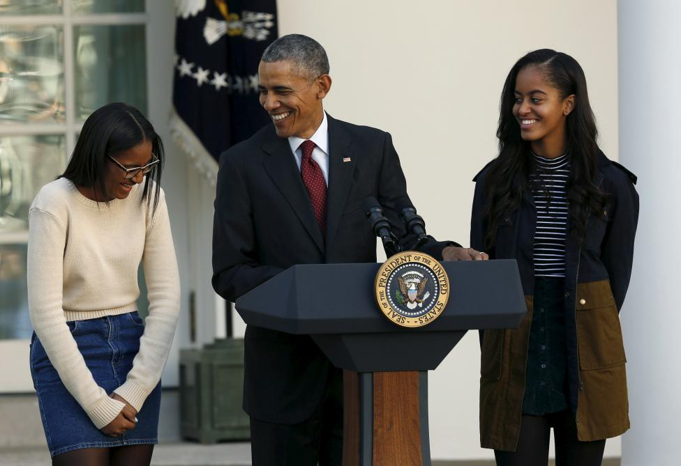 United States President Barack Obama, along with daughters Sasha (L) and Malia (R), attends the 68th annual pardoning of Thanksgiving turkey Abe (not pictured in the Rose Garden of the White House in Washington November 25, 2015. REUTERS/Gary Cameron