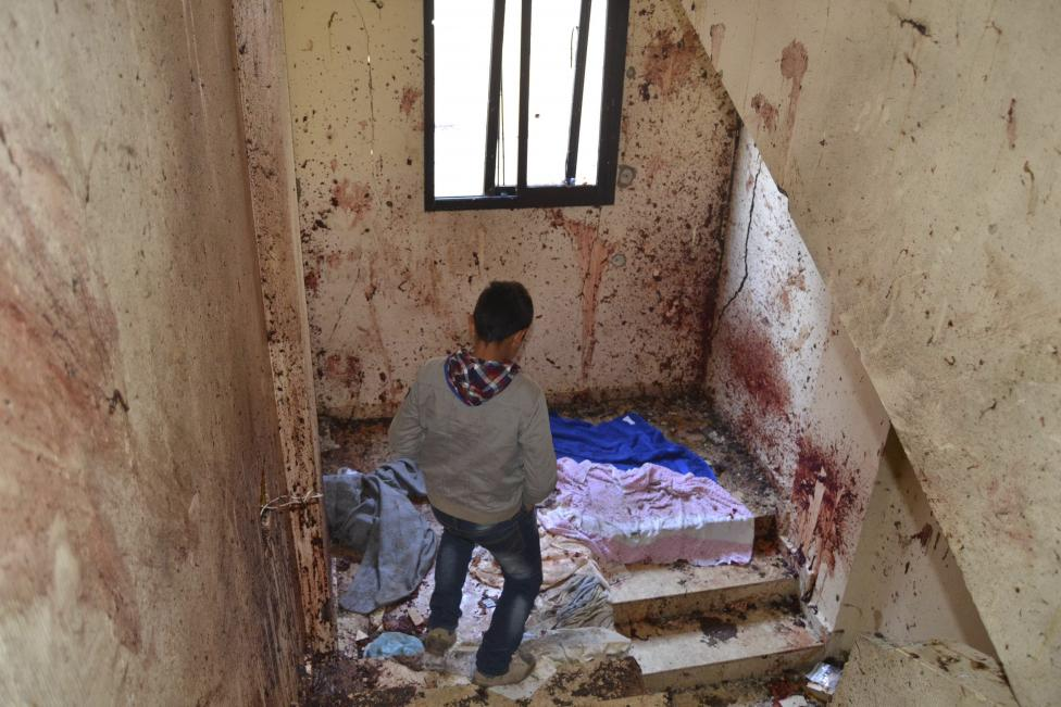 A boy walks down a staircase with splashed blood on the walls of a staircase caused by an explosion inside a building in Deir Ammar town, northeast from the city of Tripoli, Lebanon December 5, 2015. A suspected Islamist militant and two members of his family were killed in northern Lebanon on Saturday, after the man blew himself up during an army raid on his home, security and medical sources said. The raid took place in the town of Deir Ammar, northeast of the city of Tripoli. The explosion killed the wife and mother of the suspect, who was named as Mohammed Hamzeh, a security source said. At least 10 others were wounded, including four security personnel. A security source said Hamzeh was part of a group that had pledged allegiance to Islamic State. REUTERS/Fathi Al Masri