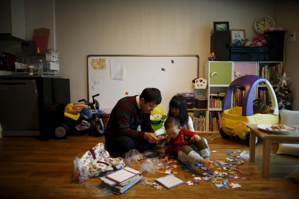 """Chung Sang-hoon talks to his daughter and son at their apartment in Seoul, South Korea, December 14, 2015. Fathers who take paternity leave were once so rare in male-dominated South Korea that they are called """"superdads"""". But their ranks are growing. REUTERS/Kim Hong-Ji"""
