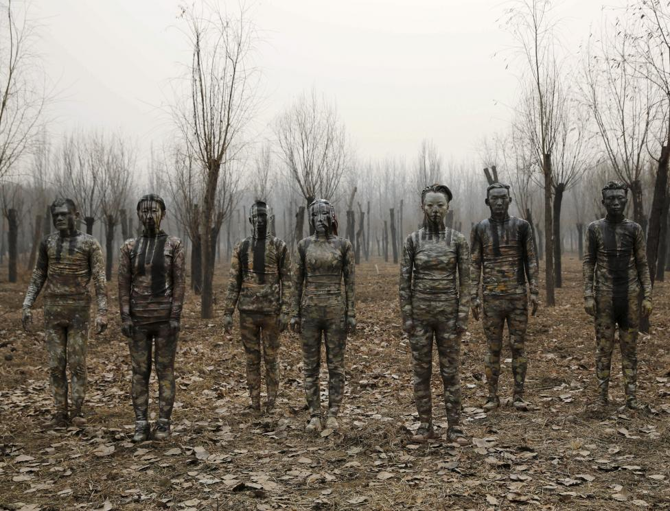 """Models painted in camouflage colors to blend in with the background pose for Chinese artist Liu Bolin's artwork """"Dongji"""", or Winter Solstice, on the second day after China's capital Beijing issued its second ever """"red alert"""" for air pollution, in Beijing, China, December 20, 2015. In this artwork, Liu wants to express his concerns about China and its people, including air pollution problem, Liu told Reuters. REUTERS/Kim Kyung-Hoon"""