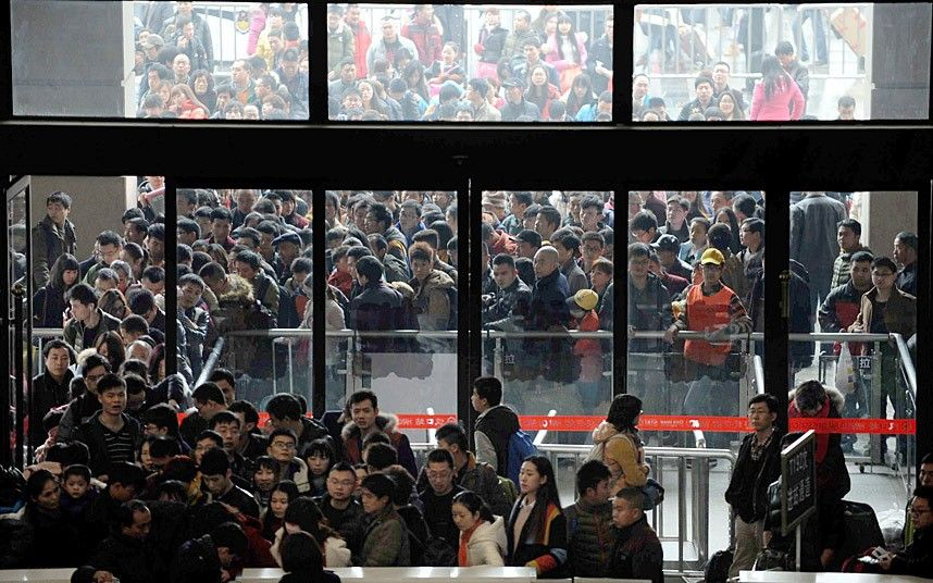 15 Feb 2015, Wuhan, Hubei Province, China --- Crowds of Chinese passengers wait for check-in at the Hankou Railway Station before taking trains to go back home for Spring Festival to celebrate the Chinese Lunar New Year in Wuhan city, central China's Hubei province, 15 February 2015. As hundreds of millions in China flock home to celebrate the Year of the Sheep, the world's biggest human migration places extraordinary pressure on roads and railways, but technology is offering new ways to find a route home. Chinese tradition requires people to gather at their family home before the Lunar New Year begins, on February 19 this year, with authorities expecting more than 2.8 billion trips to be taken over the festive period. Rail is one of the favoured ways to travel and while historically there have been endless queues at the ticket windows, China's official train booking website 12306.cn is helping to relieve co --- Image by © Imaginechina/Corbis