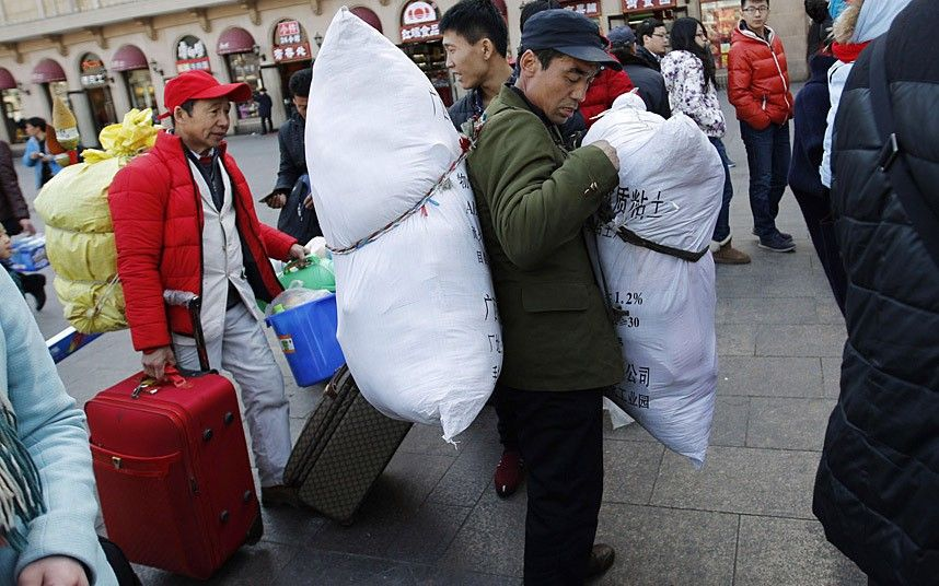 A man carries sacks as he stand in a line to enter a platform at a railway station in Beijing February 16, 2015. Chinese Ministry of Transport said a total of 2.807 billion trips are expected to be made during the 40-day Spring Festival travel rush, which started on February 4 and will last until March 16, Xinhua News Agency reported. REUTERS/Kim Kyung-Hoon (CHINA - Tags: TRANSPORT SOCIETY)