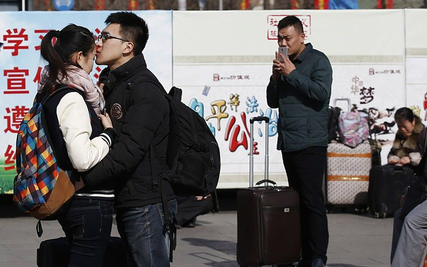 A couple kisses at a railway station in Beijing February 16, 2015. Chinese Ministry of Transport said a total of 2.807 billion trips are expected to be made during the 40-day Spring Festival travel rush, which started on February 4 and will last until March 16, Xinhua News Agency reported. REUTERS/Kim Kyung-Hoon (CHINA - Tags: TRANSPORT SOCIETY)