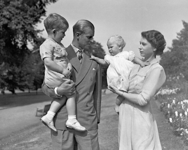 Princess-Anne-in-the-arms-of-Princess-Elizabeth-with-the-Duke-of-Edinburgh-holding-Prince-Charles-in-the-grounds-of
