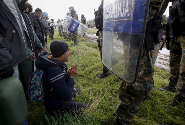 A Moroccan migrant begs Macedonian police officers to let him cross the Greek-Macedonian border near the Greek village of Idomeni November 26, 2015. Hundreds of Moroccans, Algerians and Pakistanis tried to storm the border between Greece and Macedonia on Thursday, tearing down part of the barbed wire fence at the crossing and demanding to be allowed to carry on into northern Europe. REUTERS/Yannis Behrakis