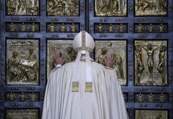 Pope Francis opens the Holy Door to mark opening of the Catholic Holy Year, or Jubilee, in St. Peter's basilica, at the Vatican, December 8, 2015. REUTERS/Max Rossi