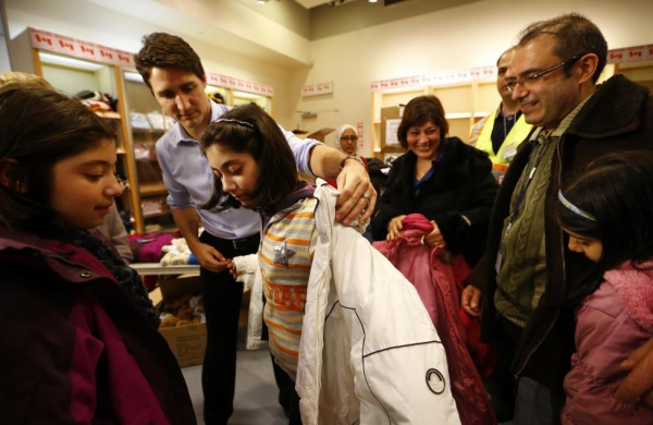 Canada's Prime Minister Justin Trudeau helps a young Syrian refugee try on a winter coat after she arrived with her family from Beirut at the Toronto Pearson International Airport in Mississauga, Ontario, December 11, 2015. REUTERS/Mark Blinch