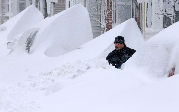 14 jonas John Silver shovels snow between buried cars in front of his home on Third Street in South Boston