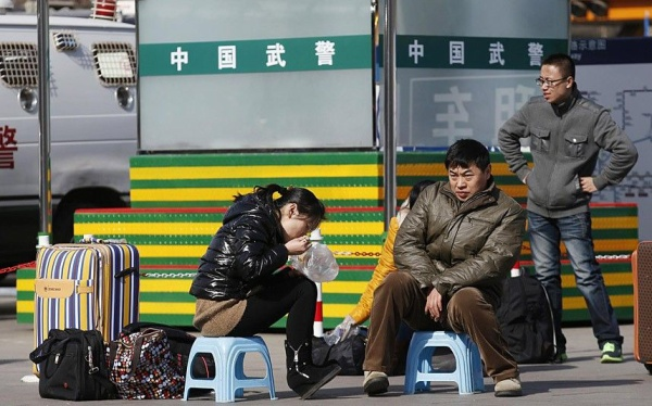 People sit on stools as they wait for their trains in front of paramilitary policemen at a railway station in Beijing February 16, 2015. Chinese Ministry of Transport said a total of 2.807 billion trips are expected to be made during the 40-day Spring Festival travel rush, which started on February 4 and will last until March 16, Xinhua News Agency reported. REUTERS/Kim Kyung-Hoon (CHINA - Tags: TRANSPORT SOCIETY)