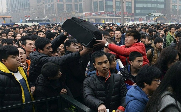 People pass a suitcase as they line up to enter a railway station in Beijing, February 15, 2015. Chinese Ministry of Transport said a total of 2.807 billion trips are expected to be made during the 40-day Spring Festival travel rush, which started on February 4 and will last until March 16, Xinhua News Agency reported. Picture taken February 15, 2015. REUTERS/Stringer (CHINA - Tags: SOCIETY TRANSPORT) CHINA OUT. NO COMMERCIAL OR EDITORIAL SALES IN CHINA