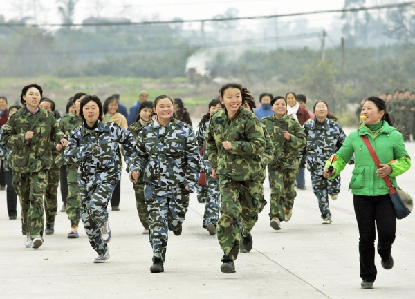 """CHENGDU, CHINA:  A class of girl students runs during a physical training exercise at the temporary campus of the """"Walking School"""" of Xu Xiangyang Education and Training Group, 22 December 2005, on the outskirts of China's southwestern city of Chengdu. Some 215 boys and girls from eight to eighteen who are considered """"uneducateable"""" students dress in camouflage jackets, sleep in trucks, study in tents, eat in the open and receive quasi-military management and physical training, culture and technology education at the boarding school. The school and families attempt to foster the children's good behaviour, independence, and the capability of studying through an """"ascetic"""" way.   AFP PHOTO/ LIU Jin  (Photo credit should read LIU JIN/AFP/Getty Images)"""
