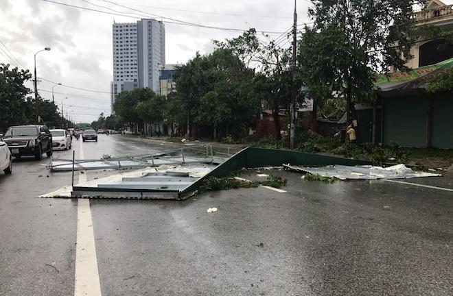 Một mái tôn của nhà dân bị tốc bay xa hàng chục mét nằm chắn ngang đường Nguyễn Sỹ Sách khiến giao thông bị hỗn loạn.