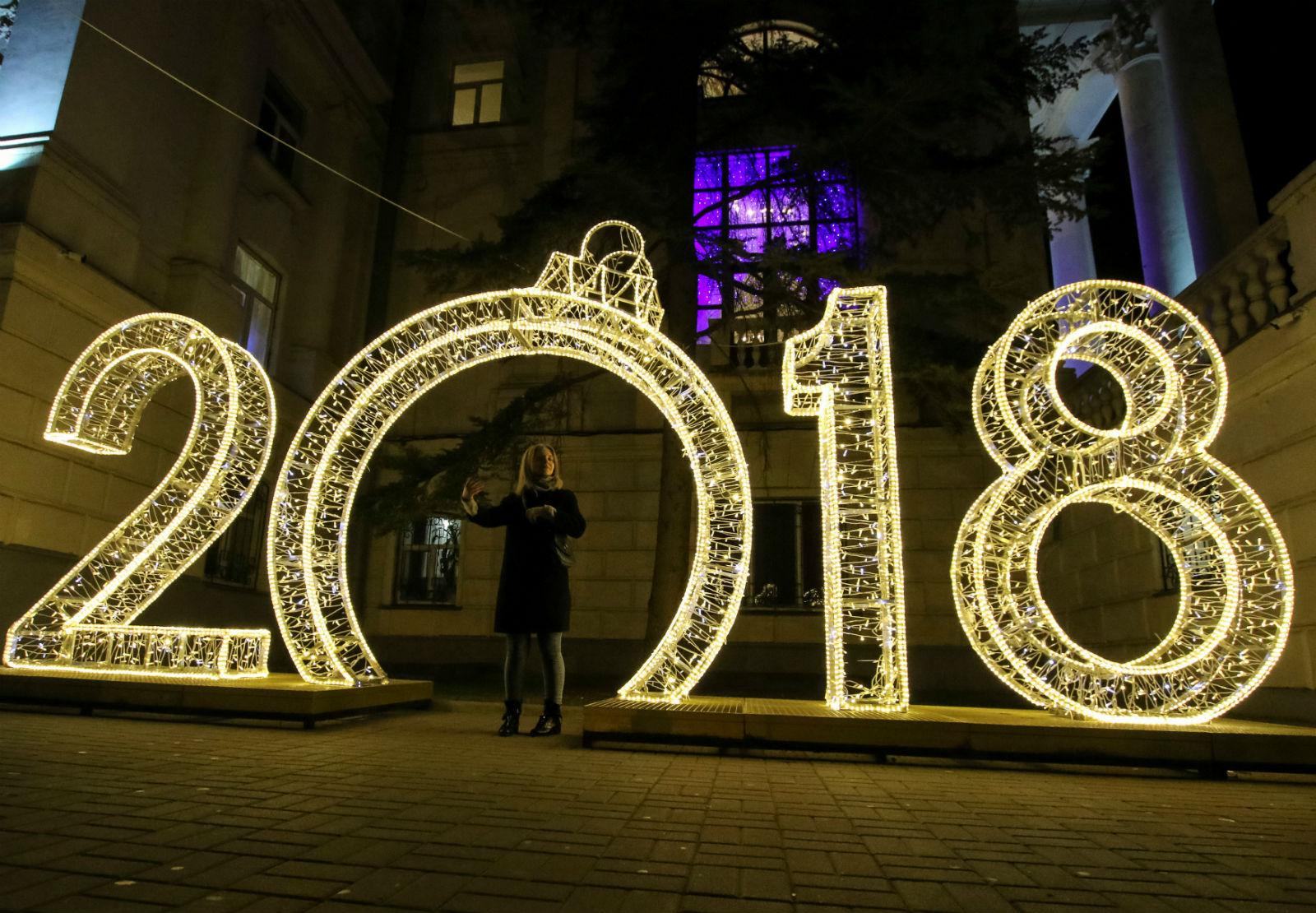 Người phụ nữ đứng dòng chữ 2018 được trang trí cách điệu bằng hệ thống đèn sáng ở Sevastopol, Crimea, Nga.