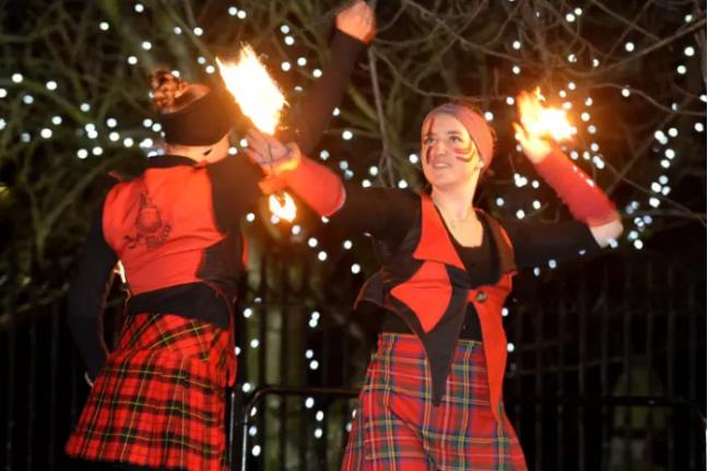 Các cô gái mặc trang phục màu đỏ, tay cầm đuốc nhảy múa trong lễ hội rước đuốc.