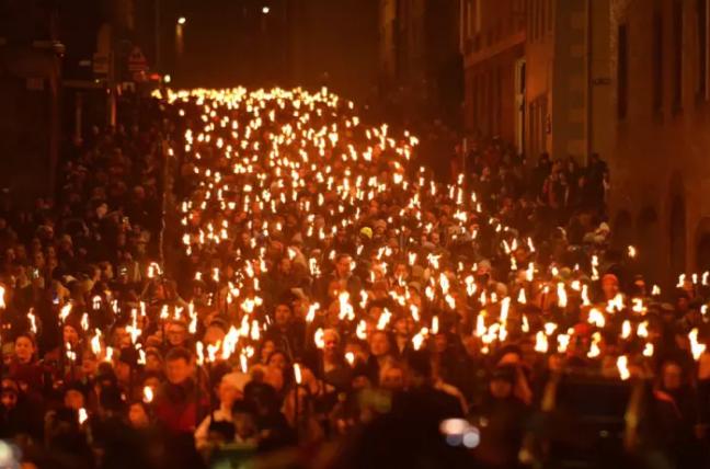 """Khoảng 2.000 người khỏa thân cầm đuốc nhảy múa, """"cháy hết mình"""" trong lễ hội. Họ đi diễu hành dọc con đường từ quảng trườngOld Town tới bên ngoài cung điện Holyroodhouse, nơi ở của Nữ hoàngScotland."""
