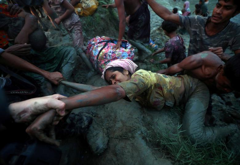 Các nhiếp ảnh gia giúp người tị nạn Rohingya vượt sông Nad khi họ băng qua biên giới Myanmar-Bangladesh ở khu vực Palong Khali, gần Cox's Bazar, Bangladesh, ngày 1/11. Hơn 600.000 người Hồi giáo Rohingya đã chạy khỏi Myanmar kể từ ngày 25/8 sau khi quân đội nước này phát động chiến dịch truy quét các phần tử nổi dậy người Rohingya tấn công các trạm kiểm soát biên giới.
