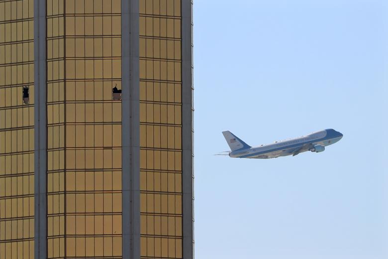 Chiếc Air Force One khởi hành từ Las Vegas qua lỗ thủng trên các cửa sổ của khách sạn, nơi Stephen Paddock tiến hành xả súng giết chết 59 người ở Las Vegas, bang Nevada, ngày 4/11. Đây được cho là vụ xả súng đẫm máu nhất lịch sử nước Mỹ hiện đại.