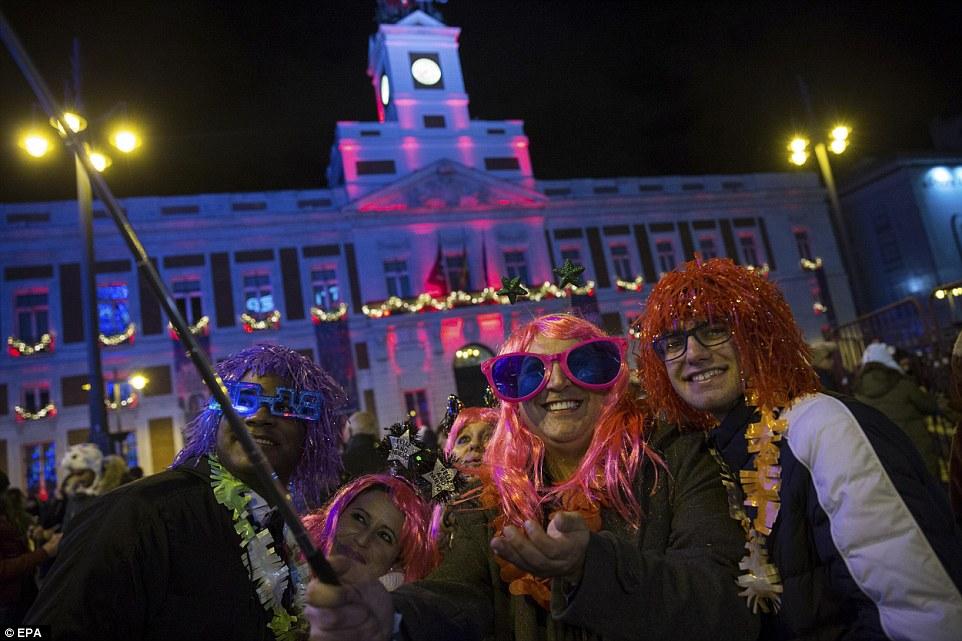Người dân tạiMadrid, Tây Ban Nha đội tóc giả và kính mắt đầy màu sắc cùng nhau chụp ảnh trong giờ phút giao thừa.