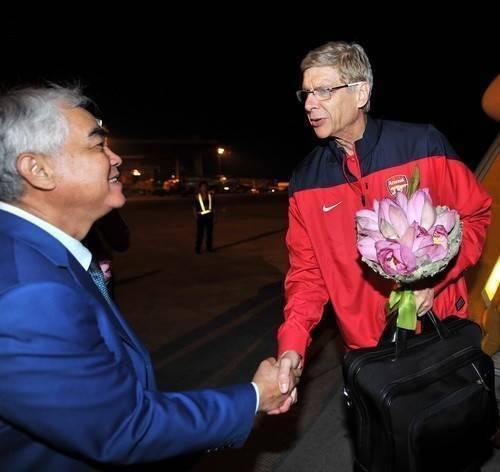 HLV Arsene Wenger được đón tiếp ngay tại chân máy bay với nón lá và hoa sen mang đặc trưng của Việt Nam.