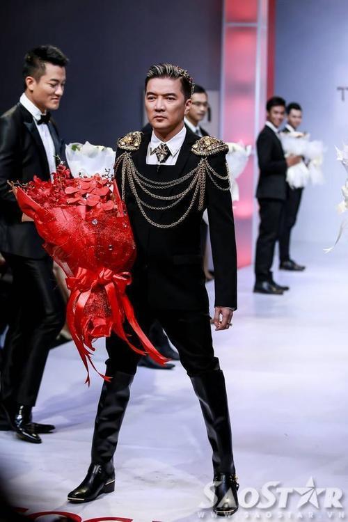 """Nam huấn luyện viên """"The Voice"""" phiên bản Việt diện bộ vest đen phối phụ kiện vàng nổi bật. Vì chiều cao có phần khiêm tốn nên anh dành hẳn một buổi trước đó để cùng stylist, nhà thiết kết lựa chọn trang phục, phụ kiện sao cho làm mình tỏa sáng trên sàn diễn nhất."""
