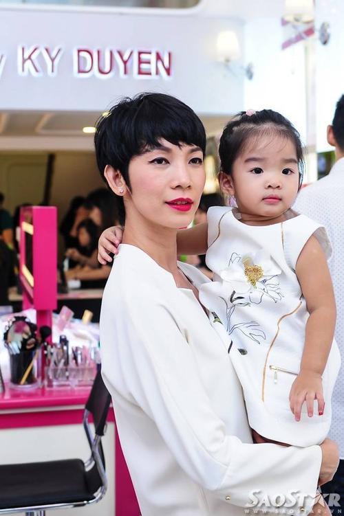 Cựu siêu mẫu Xuân Lan bế con gái đến buổi tiệc. Hai mẹ con diện trang phục tone sur tone màu trắng.