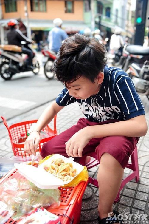 Mượn chiếc giỏ nhựa của mẹ làm bàn, Công Quốc vô tư ngồi ăn ngoài góc đường vì quá đói.