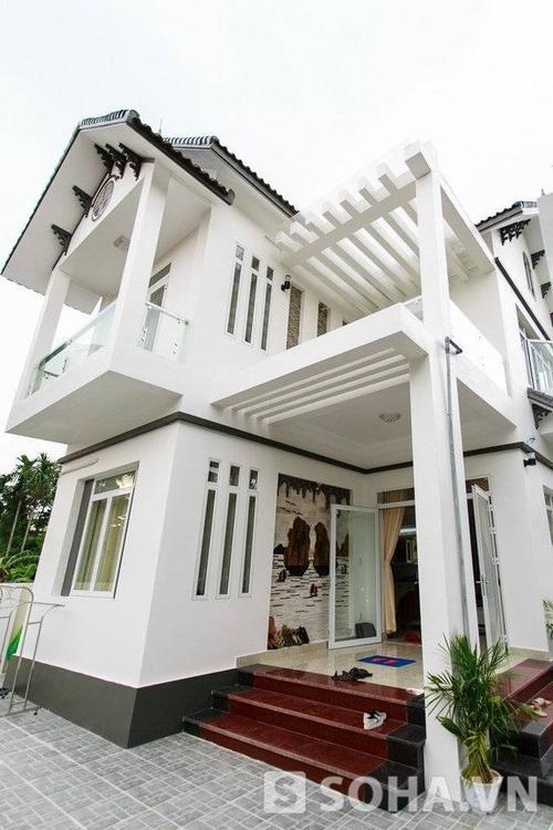 Căn nhà 2 tầng với thiết kế sang trọng, hiện đại nổi bật với màu trắng bắt mắt. Ngôi nhà này khác biệt hoàn toàn với những căn nhà cũ kỹ, thấp bé xung quanh.