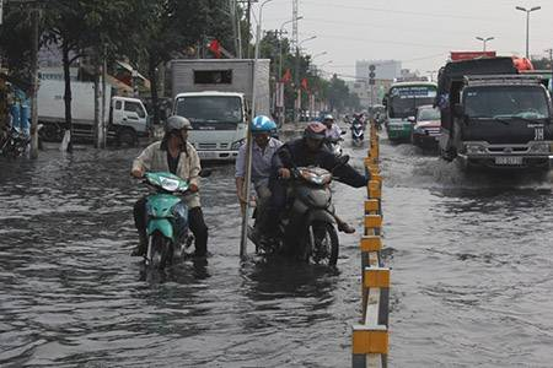 Đoạn ngập kéo dài khoảng 200 m trên đường Kinh Dương Vương (phường An Lạc, quận BÌnh Tân) gây khó khăn cho người đi đường - Ảnh: Phạm Hữu.