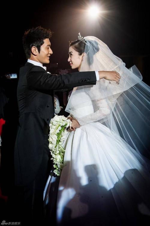 Hôn lễ Angela Baby và Huỳnh Hiểu Minh diễn ra vào ngày 8/10 tại Trung tâm triển lãm quốc tế Thượng Hải. Trong ảnh cô dâu và chú rể tình tứ trước ống kính khi vén khăn cô dâu.