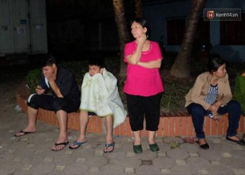 Một số cư dân tòa nhà buồn bã ngồi bên ngoài khi xuống đất an toàn.