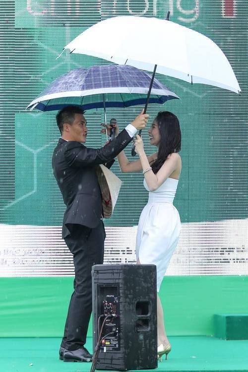 Ngay lập tức, Công Vinh tiến lên sân khấu, mang theo chiếc ô to hơn cho vợ.