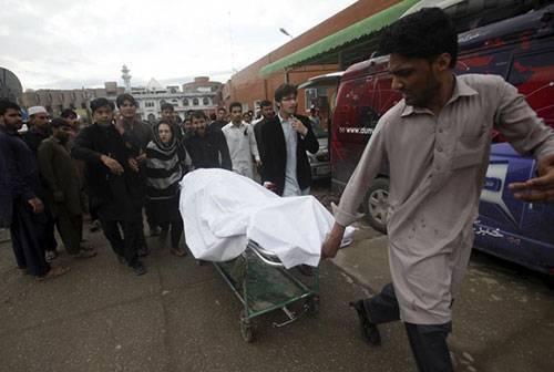 Thi thể một phụ nữ được chuyển đi tại Peshawar, Pakistan. Ảnh: Reuters.