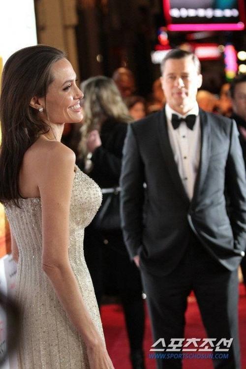 Brad Pitt ngắm nhìn Angelina rạng rỡ trước ống kính. Tài tử là người theo sát vợ trong giai đoạn cô phẫu thuật cắt bỏ bầu ngực để ngăn ngừa ung thư vú. Ngoài ra, Angie chia sẻ chính Brad giúp cô tránh được cảm giác kém nữ tính sau cuộc phẫu thuật cắt buồng trứng.