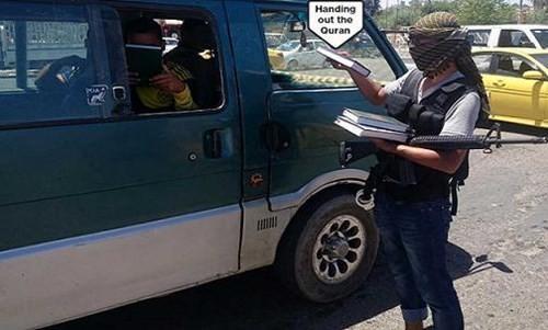 Các thành viên Nhà nước Hồi giáo - IS phân phát kinh Coran tại 1 trạm kiểm soát của chúng.