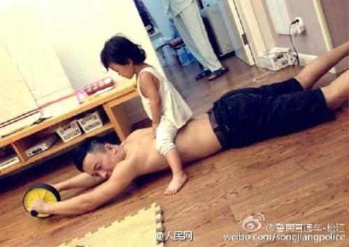 Cô bé thích thú ngồi trên lưng cha trong bài tập lăn tạ.