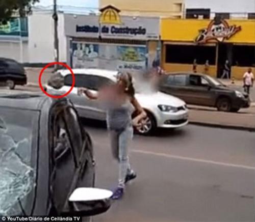 Người vợ lấy một tảng đá sắc nhọn bên đường ném vỡ cửa kính xe ô tô của chồng.
