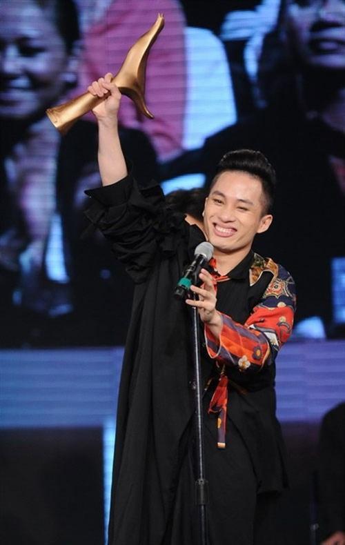 Ca sĩ Tùng Dương hào hứng giơ cao chiếc cúp Cống hiến trong một lần nhận giải.