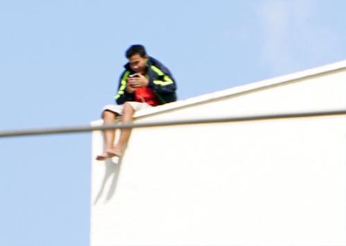 Nam thanh niên ngồi vắt vẻo trên tầng thượng tòa nhà trung tâm thương mại.