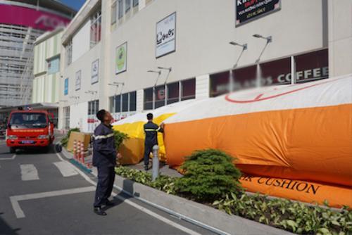 Lực lượng cứu hộ trải túi khí đề phòng nam thanh niên nhảy xuống.