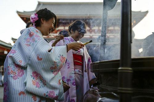 Các cô gái Nhật Bản mặc kimono, đốt hương tại đền Sensoji, Tokyo, trước thềm năm mới.