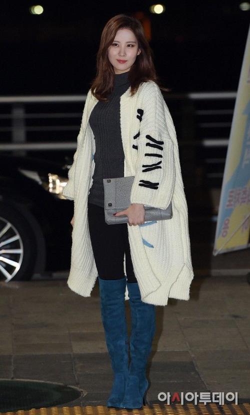Em út Seohyun nổi bật trong chiếc cardigan len dày dáng dài, đối lập với áo và quần tông đen.