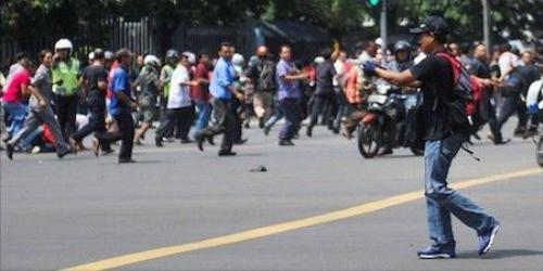 Hình ảnh do phóng viên Veri Sanovri, Tân Hoa xã của Trung Quốc cho thấy một người đàn ông trong trang phục màu đen, đội mũ, cầm súng và chạy trong khu vực Jalan MH Thamrin, gần trung tâm mua sắm Sarinah sáng 14/1. Ảnh: Tân Hoa xã