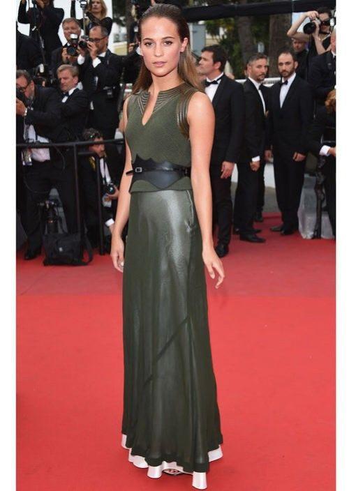 Alicia Vikander đài các trong bộ váy kaki màu xanh rêu có dây thắt lưng bằng da của thương hiệu LV trong bộ sưu tập Cruise 2016 tại buổi chiếu phim Sicario ở Cannes 2015.