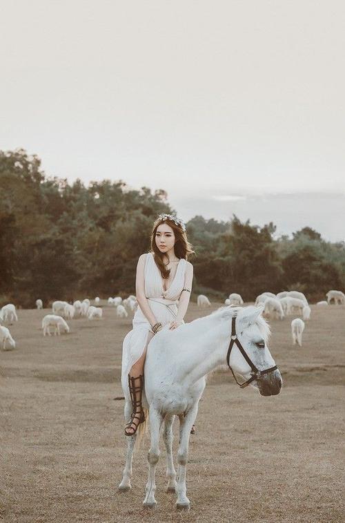 Bạn diễn của cô là những chú ngựa và cừu trắng muốt đang ung dung gặm cỏ xung quanh