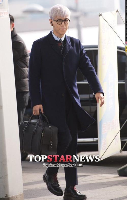 T.O.P chỉnh chu với bộ vest tối màu, đeo kính gọng tròn, xách túi như một quý ông trẻ. Trang phục của rapper cá tính không nhàm chán nhờ mái tóc tím nhạt nổi bật.