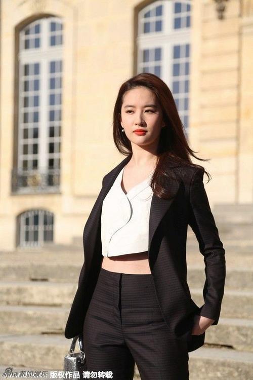 Người đẹp nổi bật với bộ vest cá tính phối áo crop-top trắng. Cô xách túi màu bạc của Dior.