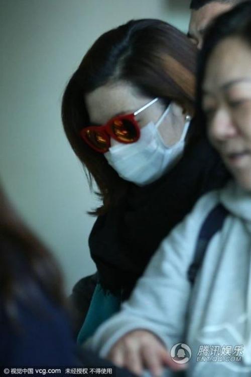 Selina cúi thấp mặt, đeo kính và khẩu trang né ống kính.