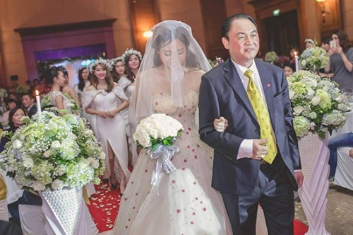 Cô dâu Trà My phủ voan che mặt và khoác tay bố tiến vào làm lễ.