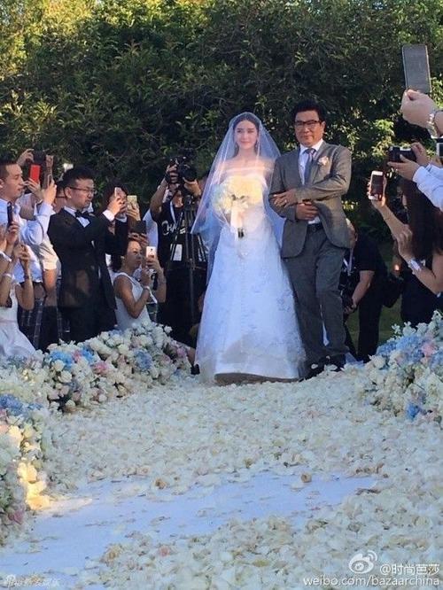Cô dâu Lưu Thi Thi xuất hiện bên cạnh cha, cô được ông nắm tay tiến vào sảnh chính của hôn lễ.