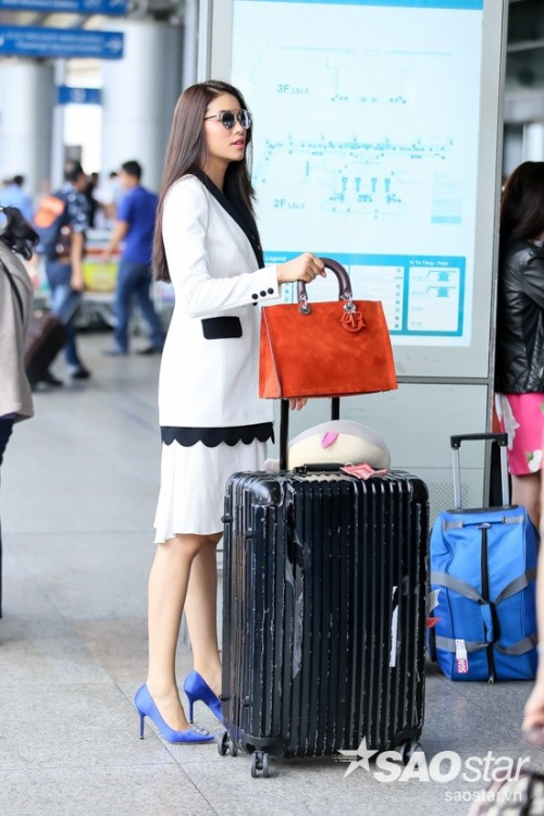 Người đẹp vui vẻ đứng chờ ê-kíp của mình hỗ trợ phần ký gửi hành lý.